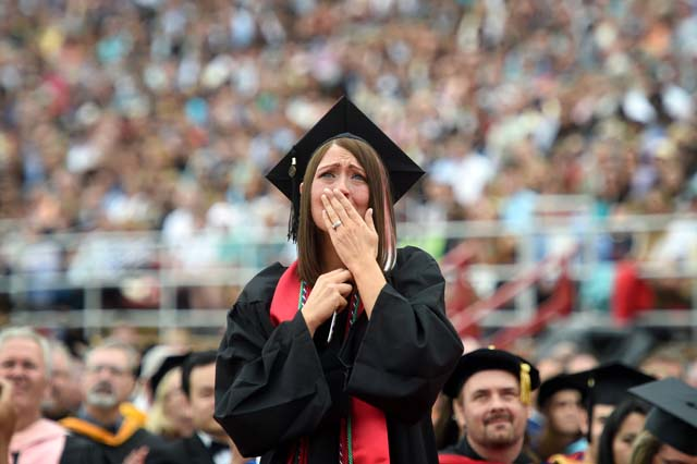 Malory Jade Mallery reacts while hearing a congratulatory video message from her husband, who is serving overseas in the military, during the Liberty University commencement ceremony in Lynchburg, Va., May 10, 2014.   (Photo by Parker Michels-Boyce/The News & Advance)